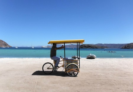 A beach vendor peddling by
