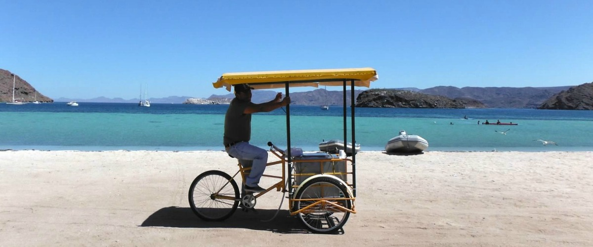 A vendor pedals by on this gorgeous beach