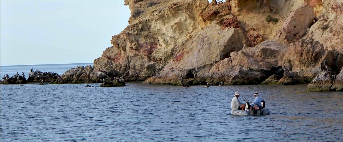 Fishing near some colorful rock formations